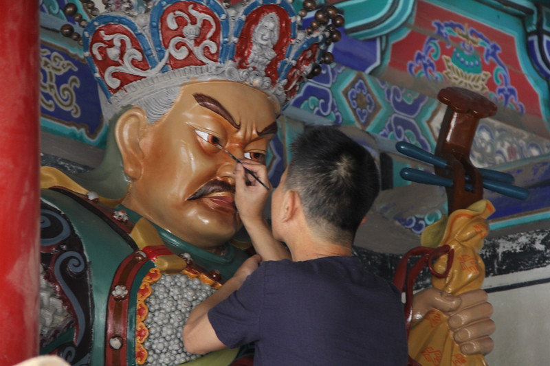 A pipa toting Buddhist immortal gets a touch up at the Shaolin Zhongyue Temple. June 21, 2017