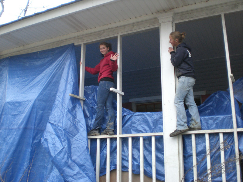 Regina and Jaime tarping the furniture they moved onto the porch