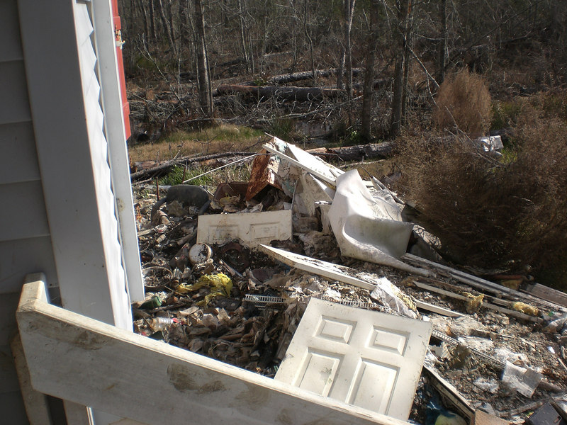 Debris outside house that still needs to be gone through more than a year later...