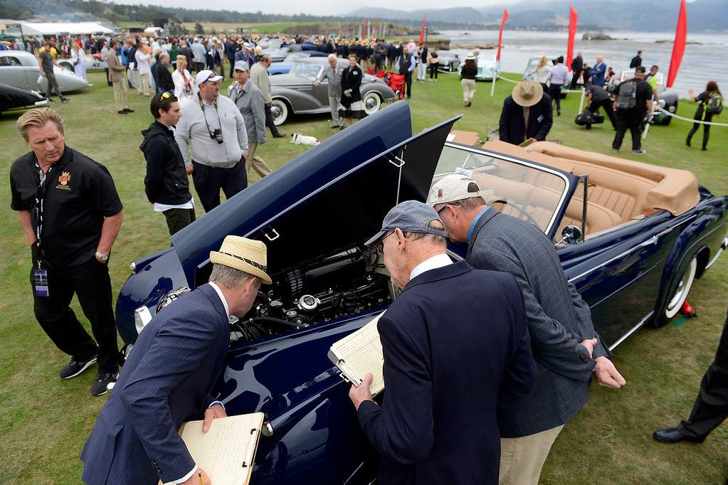 . Judges look over a 1940 convertible coupe at the Pebble Beach Golf Links during the Pebble Beach Concours d\'Elegance on Sunday, Aug. 20, 2017.  (Vern Fisher - Monterey Herald)