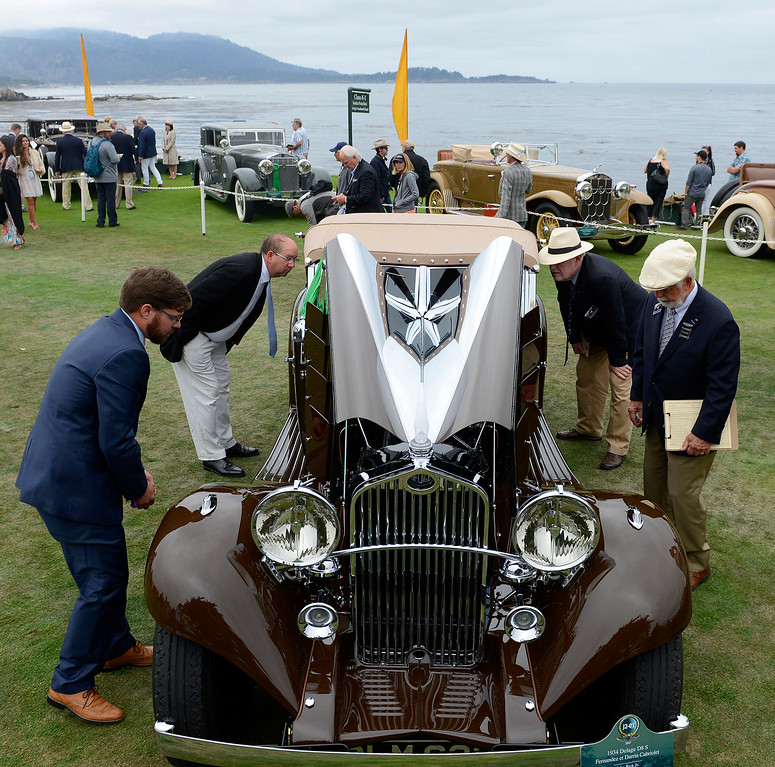 . Judges gather around a 1934 Delage D8 S Fernandez et Darrin Cabriolet while on display at the Pebble Beach Golf Links during the Pebble Beach Concours d\'Elegance on Sunday, Aug. 20, 2017.  (Vern Fisher - Monterey Herald)