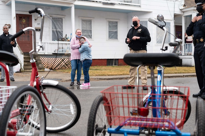 Along with her Mom, Rita, Sierra Fletcher awaits a surprise gift from the police-based charity Pedal Thru Youth.  Bob Charland, pictured next to Sierra, is a deputy in Hampden County, MA and the organization's founder.  Pedal Thru Youth promotes an active and healthy lifestyle among youths by donating bikes and helmets to low-income, or needy, families.