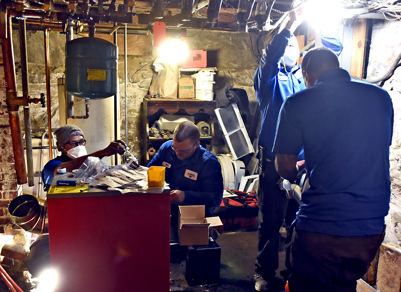 Workers from A. Fagundes Plumbing & Heating, work on installing a new boiler donated from F.W.Webb, at the home of Peggy Scholefield in Pepperell, her home houses foster children and strugging veterans. SUN/ David H. Brow