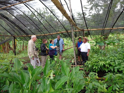 """Pej Pem staff member Pascual (wearing hat), affectionately known as """"Posh,"""" explains what different plants are being grown in this protected garden. More photos of the Pej Pem ecology center may be seen here."""