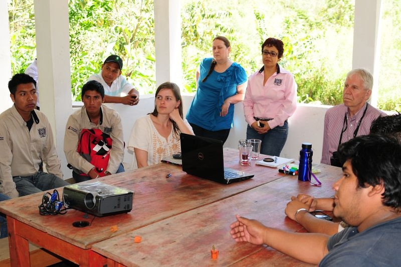 Students take the lead in giving a presentation for program participants. Their professor (in pink blouse) looks on.