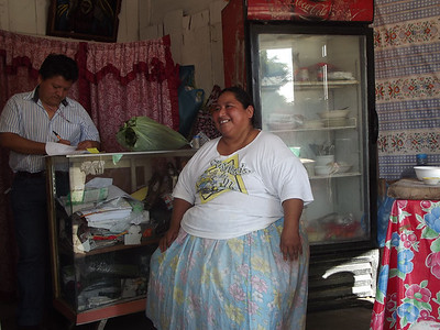 Manuela, an Amextra micro-finance partner, talks with Jorge Perez, director of Amextras' Palenque microfinance department. She was able to open a small restaurant with funds received through Amextra.