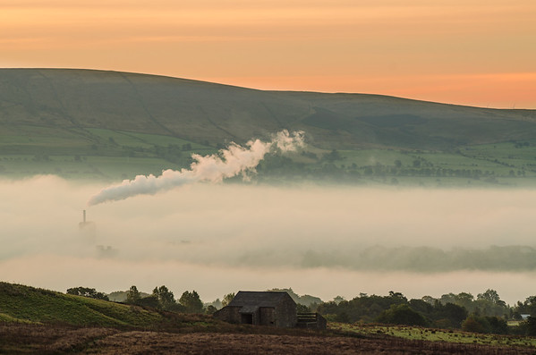 Chimney at Clitheroe cement works rises above the fog in the Ribble Valley.