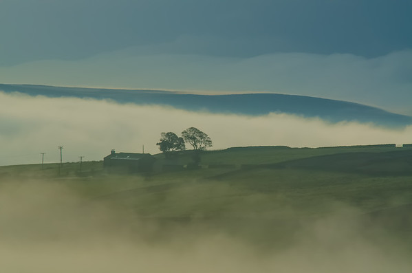 On the road to Roughlee from Barley with mist rolling in the valley.