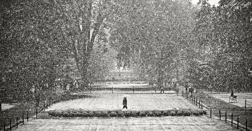 People walk along Pattee Mall on Thursday, Oct. 15, amidst a surprise snowfall, the first of the season, stemming from a wintry mix system moving across the state. While no significant accumulation is expected on most surfaces, slippery conditions exist.