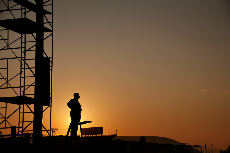 Penn State Blue Band director Dr. O. Richard Bundy is silhouetted by the sunrise with Mt. Nittany and Beaver Stadium behind him during a 7 a.m. gameday rehearsal at the Blue Band Building in University Park, Pa. before the Penn State football home opener against Akron on Sept. 5, 2009. Photo by Andy Colwell