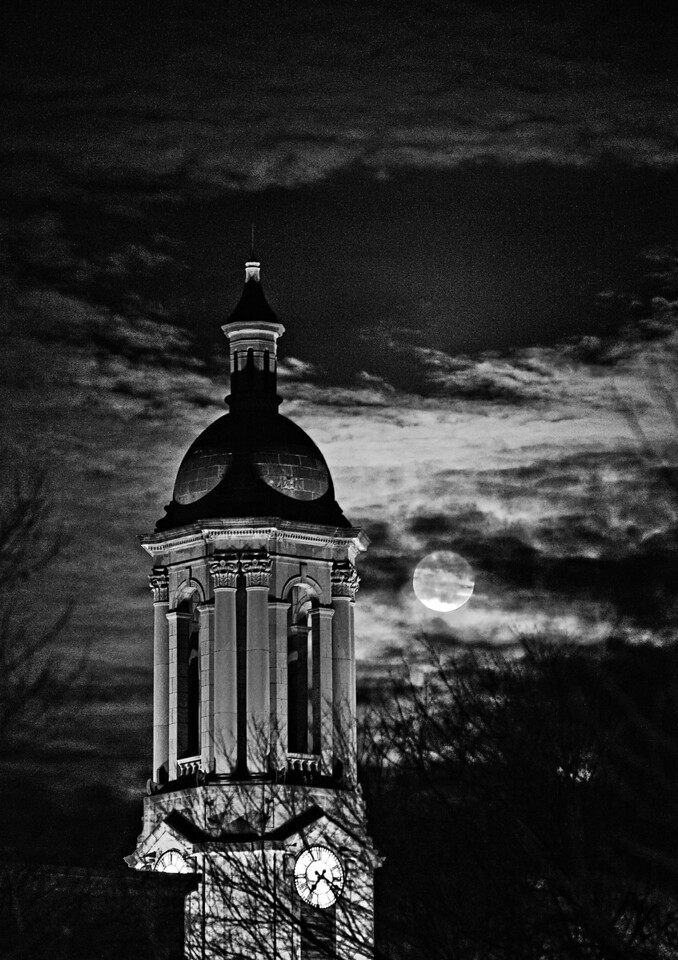 A near-full moon peers out through clouds behind Penn State's Old Main building on Jan. 30, 2010. Photo by Andy Colwell