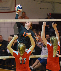 Sydney Buell (17) slams ball at Abby Wright (17) and Meghan McCann (12).