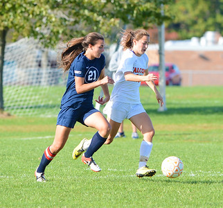 Evie Ciaccia (24) races Carly Hickey (21) to the ball.