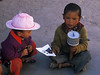 Chidren on Lhasa street with prayer wheel and picture of Dali Lama (?)
