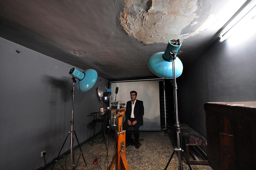 Man sitting in an old photo studio, Isfahan, Iran.