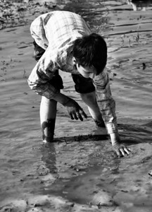 A young boy trying to catch a fish by hand, Isfahan, Iran.