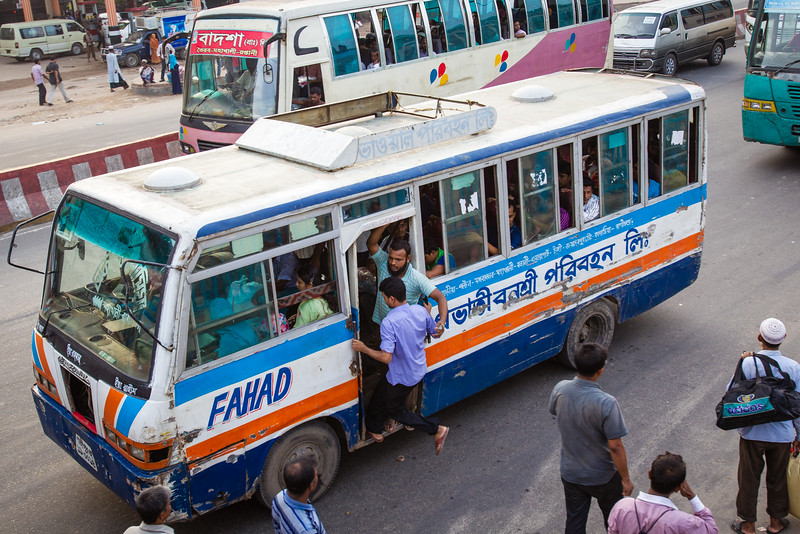 The busses do not stop to pick-up passengers (except for the elderly). Instead the fellow in the doorway hawks for fares and helps them come aboard.