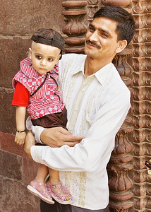 Dad and daughter in Delhi, India.  The eye make- up is to make the child less attractive--the eyes are windows to the soul and making them uglier keeps bad things away.