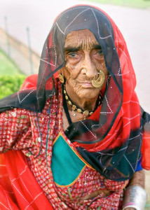 Granmother from Rajasthan State in Northeast India.  Her dress and use of jewelery are unique to her tribe.  Her necklace signifies her marital status.  Her daughter--also in these colors and with the same jewels--and grandaughter were with her.  The teen-aged grandaugher was in shorts and a t-shirt with flip-flops.