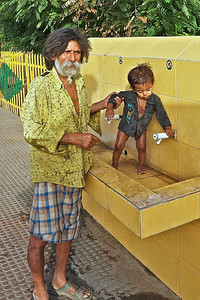 At the Ranthambhore, India Train Station a father bathes his child in the public faucet