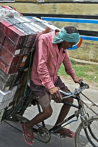 Man carrying a large load through the streets of Agra.  It is over 120 degree F.