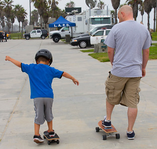 Father teaching son to skate board at Venice