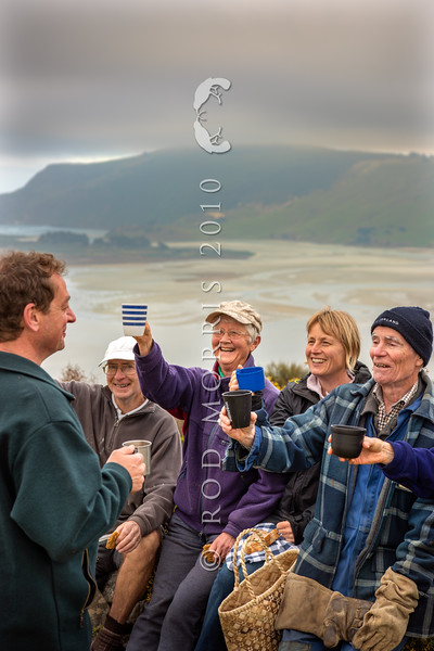 DSC_7846  OPBG community trappers and volunteers (from right), John Parker,    , Moira Parker, and  , raise their mugs to OPBG sponsor and supporter Norcombe Barker (left), on a chilly afternoon overlooking Hoopers Inlet. Photographed from the top of Peggy's Hill, Otago Peninsula for Predator Free 2050 Ltd *