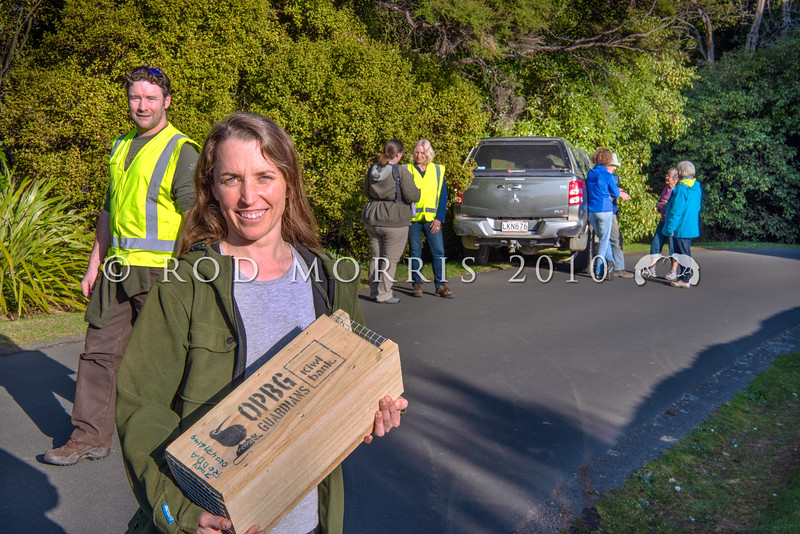 DSC_7815 OPBG Community Engagement Team Leader Marcia Dale holds a trapping tunnel, while previous Project Manager Nathan McNally walks past, while a group of Otago Peninsula Guardians meet in the background. Photographed in Dunedin for Predator Free 2050 Ltd *