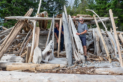 Susan and Murray in driftwood shelter on Rebecca Spit