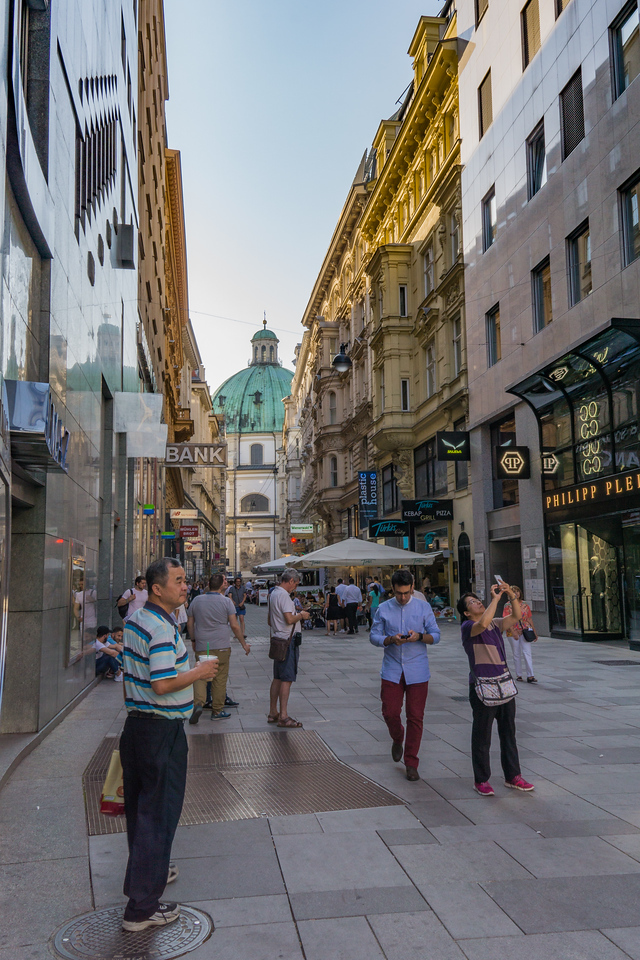 Vienna street scene with dome of Hofsburg Palace at end of block
