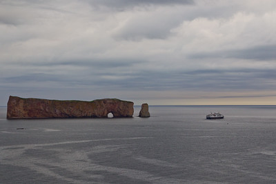 Tour boat passes Perce Rock in early morning light