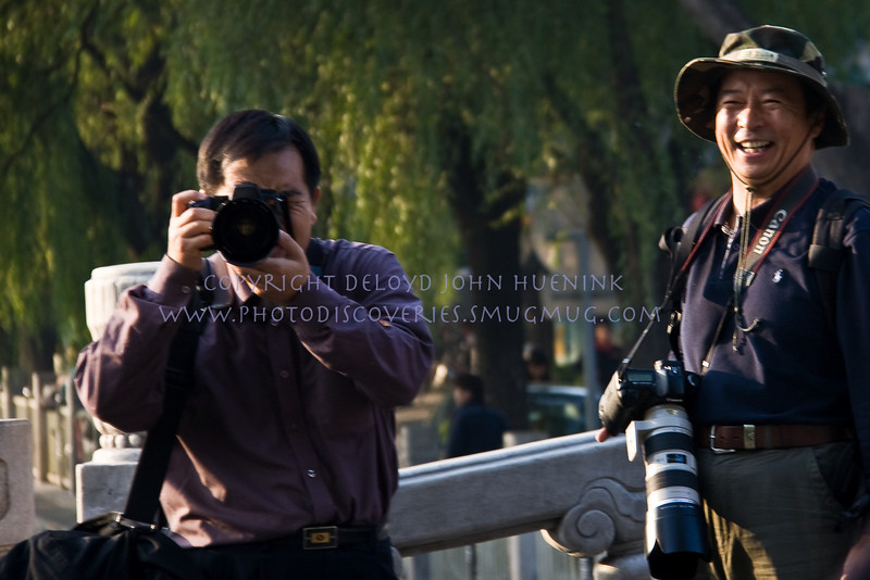 "YOU TAKE MY PICTURE, I'LL TAKE YOURS<br /> We were in Beijing, China, and these two were fascinated with my lens and ""look"" and were taking a picture of we strange westerners.  They are shooing Canon as I do.  I saw them, smiled and pointed my camera at them.  We all laughed.   Laughter...a universal language.  People are so similar all aroundr the world..."