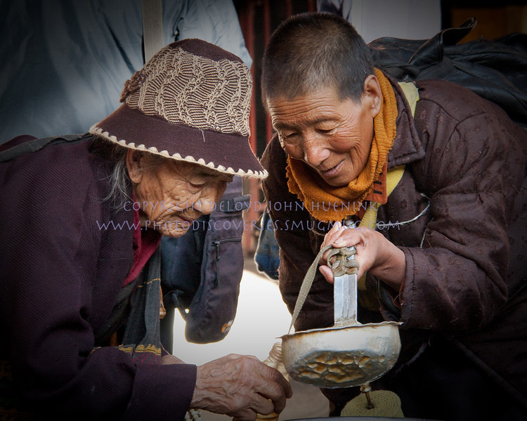 "HELPING HAND<br /> Two strangers meet outside of the temple in Lhasa, Tibet.  The older lady wants to take some ""Holy Water"" home with her, but needed help filling her bottle from the huge ladle.  The younger lady, a stranger, came to help.  Gave her a gift."
