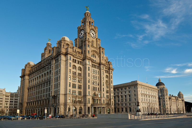 "The Royal Liver Building in the foreground, with the Cunard Building and the Port of Liverpool Building to its right.  Known as the ""Three Graces""."