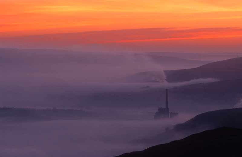 Dawn over Hope Valley and the cement factory during a period of inversion.  Peak district, Derbyshire