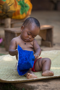 Malagasy baby playing with hat
