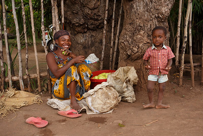 Malagasy woman with child selling fruits, Nosy Be port, Madagascar