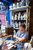 Ceramics shopkeeper watches passing tourists.  Rouen, France.