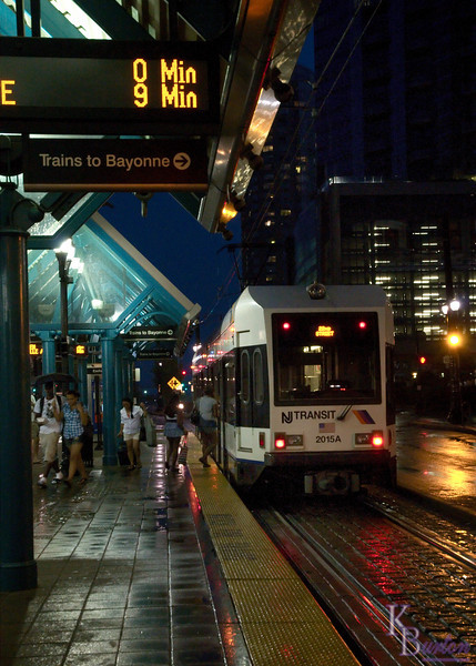 I find the Jersey Light Rail stations very interesting subjects to photograph. Here the Exchange Place station looks kind of picturesque at night in the rain.