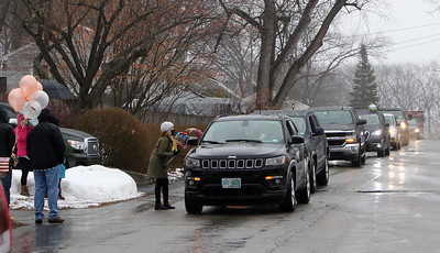 Drive-by parade past the home of Dot Dinopoulos of Dracut celebrates her 100th birthday. Daughter-in-law Karen Dinopoulos of Dracut accepts gifts from passing cars. (SUN/Julia Malakie)