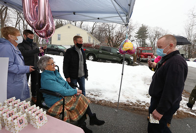Drive-by parade past the home of Dot Dinopoulos of Dracut celebrates her 100th birthday. Dinopoulos talks to next door neighbor, Dracut firefighter Brian McCarthy. (SUN/Julia Malakie)