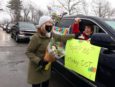 Drive-by parade past the home of Dot Dinopoulos of Dracut celebrates her 100th birthday. Daughter-in-law Karen Dinopoulos of Dracut take flowers from Rosie Kenney of Dracut, in car, and hands her a Smuckers sample in a bag. (SUN/Julia Malakie)