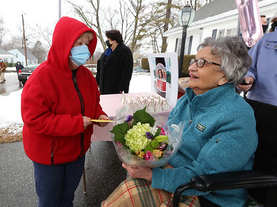 Drive-by parade past the home of Dot Dinopoulos of Dracut celebrates her 100th birthday. Next door neighbor Eileen Haggerty of Dracut, left, gives Dot a card and flowers. (SUN/Julia Malakie)