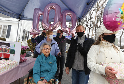 Drive-by parade past the home of Dot Dinopoulos of Dracut celebrates her 100th birthday. Dinopoulos, seated, with, from left rear, grandson Jeff Dinopoulos of Chester, N.H., Mary Sweeney of North Chelmsford (whose son is married to Dot's daughter), grandson Corey Dinopoulos of South Boston, son Greg Dinopoulos of Dracut, and Jeff's wife Sharon Dinopoulos. (SUN/Julia Malakie)