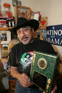 David Flores with a plaque that commemorates his being the first Mexican American on Lorain City Council.  photo by Chuck Humel