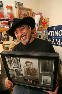 28APR10 15 Minutes, David Flores, the first Mexican American on Lorain City Counci, shoes holds a photo collage of his dad Pete Flores, Sr.,--a US Citizen, who moved north from anti-Mexican sentiments in Texas and served in the US Army in WWII as an MP.  photo by Chuck Humel