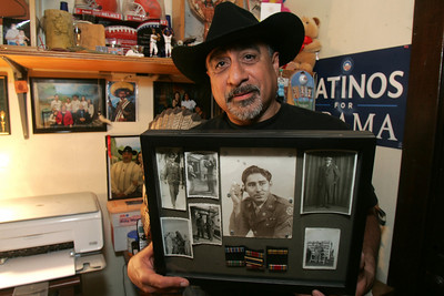 David Flores, the first Mexican American on Lorain City Counci, shoes holds a photo collage of his dad Pete Flores, Sr.,--a US Citizen, who moved north from anti-Mexican sentiments in Texas and served in the US Army in WWII.  photo by Chuck Humel