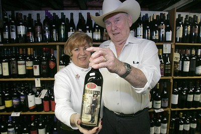 23DEC09  Richard Currier holds up a bottle of Gunfighter red wine price at around $20 from California that impressed him.  His wife Rose, left and he are co-owners of the Amherst Party Shop.   photo by Chuck Humel