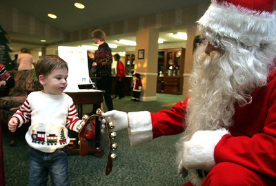 15 Minutes Santa Claus lets 20-month-old Jamie Snyder of Avon Lake jingle the bells that go around the neck of Rudolph. photo by Chuck Humel