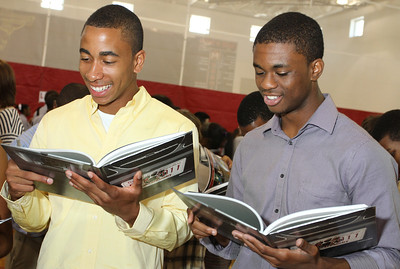After a May 11 awards program at Our Lady of Mercy High School, the students received their yearbooks. Pierce Vincent, left, stands with fellow senior Daylon Francois as they look over moments from the 2010-2011school year. Vincent will attend the University of Georgia, Athens.